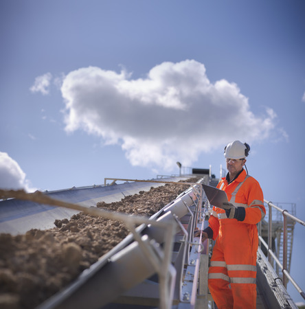 mined: Worker with clipboard by conveyor belt