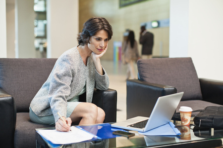 notations: Businesswoman working in lobby LANG_EVOIMAGES