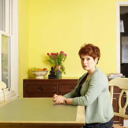 indignant: Woman sitting at kitchen table LANG_EVOIMAGES