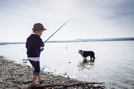 Boy fishing with dog in creek LANG_EVOIMAGES