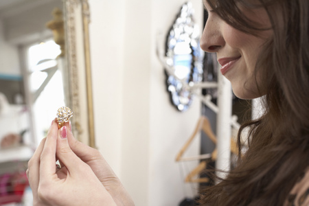 browses: Woman examining ring in store LANG_EVOIMAGES