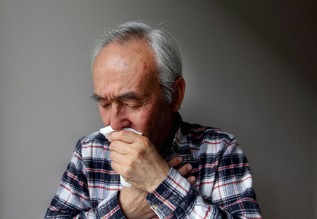 coughing: Older man coughing into napkin LANG_EVOIMAGES