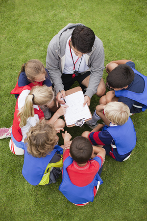 review: Coach talking to childrens soccer team