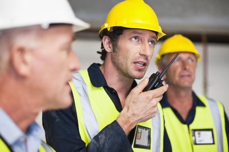 Workers using walkie talkie on site LANG_EVOIMAGES