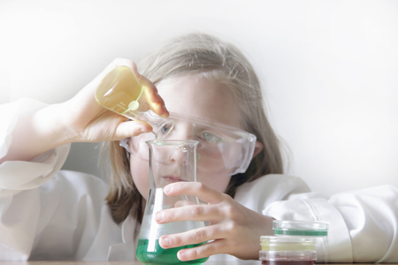 information age: Girl pouring liquid into beakers
