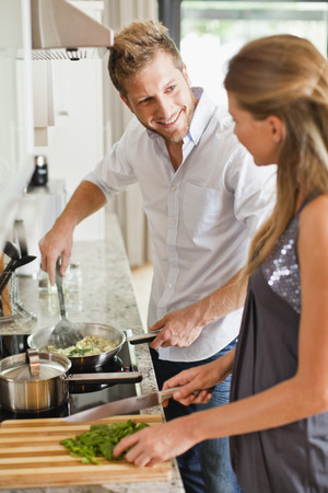 shared sharing: Couple cooking together in kitchen LANG_EVOIMAGES