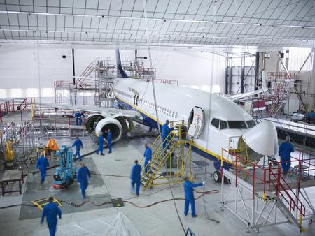 high flown: Workers in airplane hangar LANG_EVOIMAGES