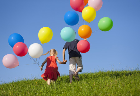 ascends: Children with colorful balloons in grass