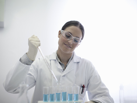 accurately: Scientist pipetting liquid in test tubes LANG_EVOIMAGES