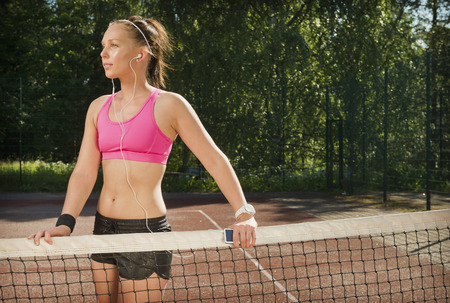 Woman in headphones on tennis court