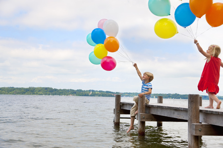 Children holding balloons on wooden pier