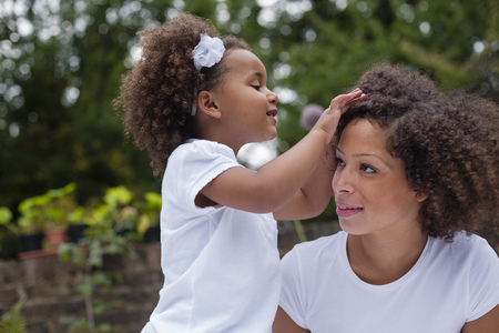 Girl playing with mothers hair outdoors LANG_EVOIMAGES