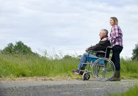 Woman pushing father in wheelchair