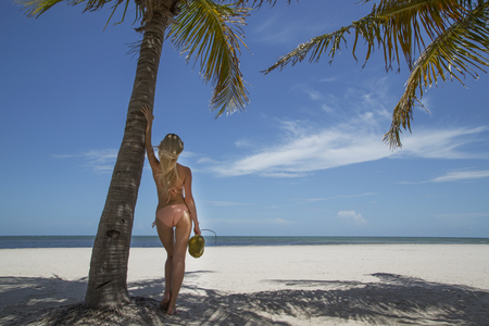 Woman holding tropical fruit on beach LANG_EVOIMAGES