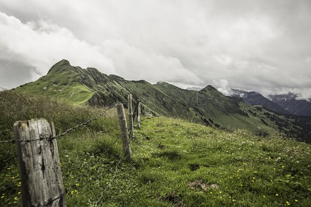 mountainous: Wire fence on grassy rural hillside LANG_EVOIMAGES