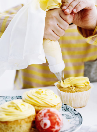 tempted: Hands icing cupcake on table