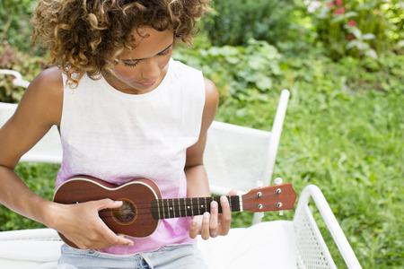 Woman playing ukulele in backyard