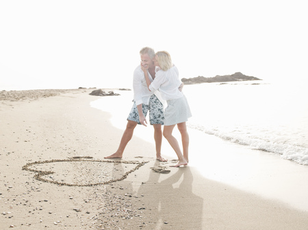 smooching: Couple drawing heart in sand on beach LANG_EVOIMAGES