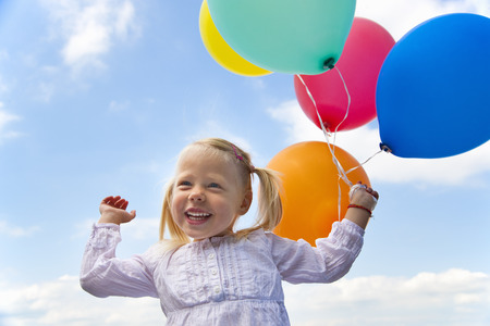 Girl holding bunch of balloons outdoors LANG_EVOIMAGES