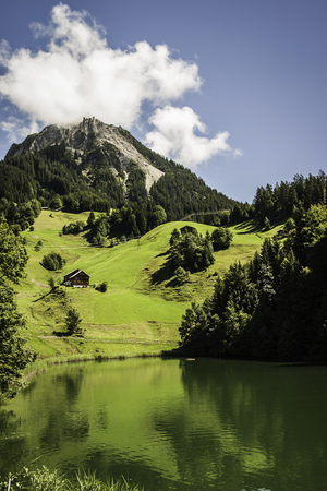 remoteness: Grassy hillside by still rural lake