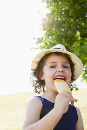 low spirited: Girl eating popsicle outdoors LANG_EVOIMAGES