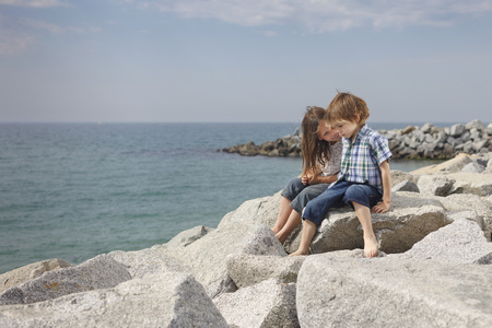 brotherly love: Children talking on rocks at beach LANG_EVOIMAGES