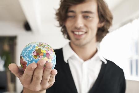 Teenage boy holding miniature globe