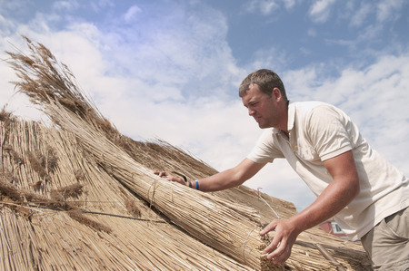 Man working on straw roof