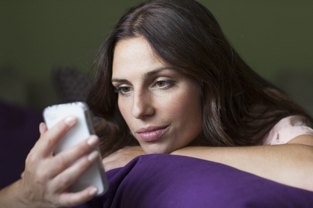 Enigmatic woman using cell phone in bed LANG_EVOIMAGES