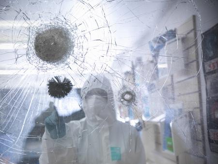 Forensic scientist at shattered window LANG_EVOIMAGES