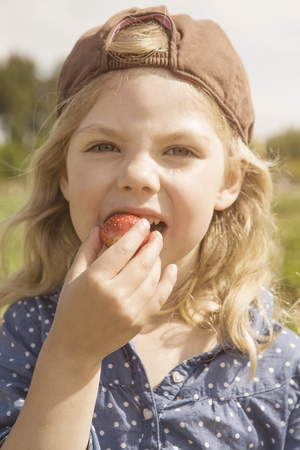 Girl eating strawberry outdoors LANG_EVOIMAGES