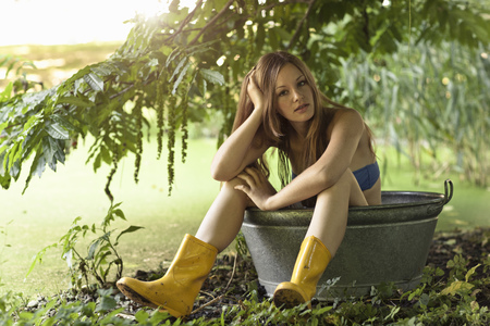 Woman sitting in bucket in garden LANG_EVOIMAGES