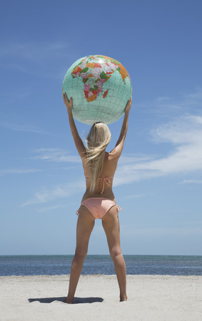 blue waters: Woman holding globe on beach