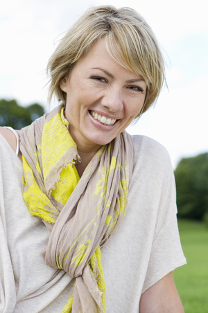 scarves: Smiling woman sitting in park LANG_EVOIMAGES