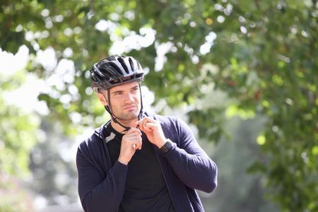 preparedness: Man tying on bicycle helmet outdoors