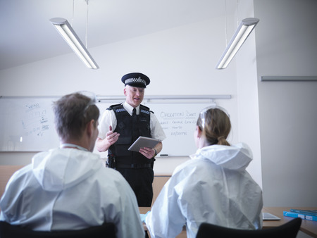 power operated: Policeman talking to forensic scientists