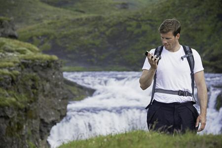 Hiker using cell phone on hillside