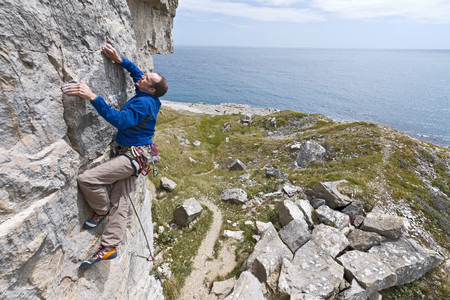 adventuresome: Climber scaling steep cliff face