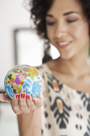 Businesswoman holding miniature globe