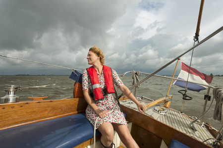 safe water: Woman steering boat on rocky water