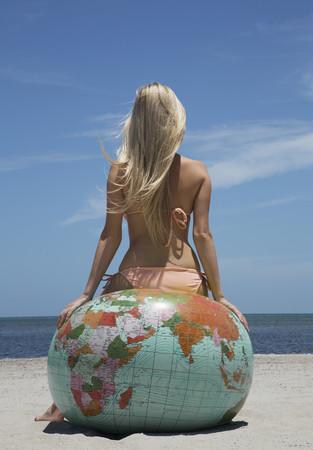 Woman in bikini sitting on globe LANG_EVOIMAGES