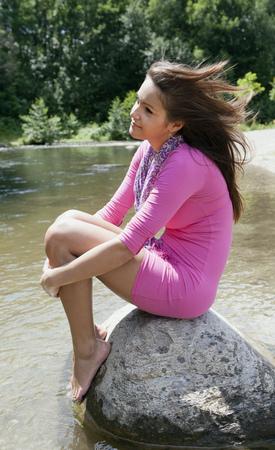 Teenage girl sitting on rock in stream LANG_EVOIMAGES