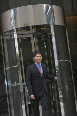 exiting: Businessman exiting revolving door LANG_EVOIMAGES