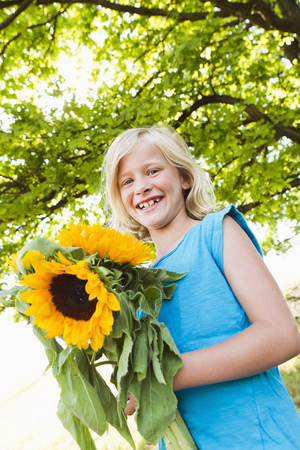 gratify: Smiling girl carrying sunflowers
