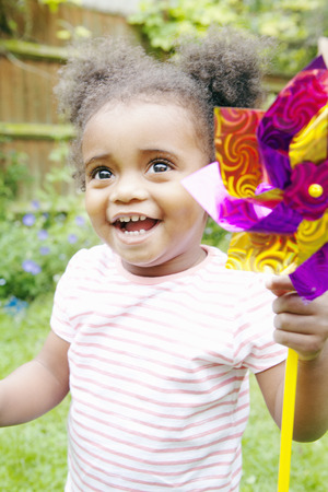 whimsy: Smiling girl playing with pinwheel