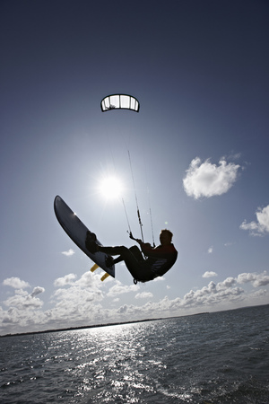 jeopardizing: Man kite surfing on calm water