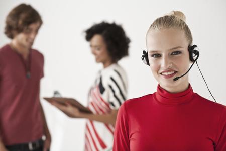 handsfree telephones: Businesswoman wearing headset in office