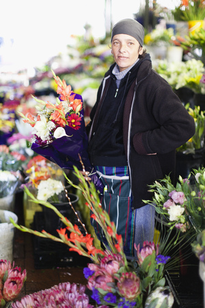 Florist with bouquet of flowers at stand