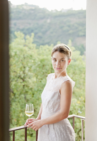Woman having wine on balcony