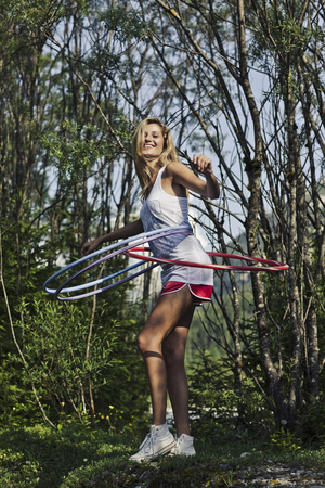 low spirited: Woman hula hooping in forest LANG_EVOIMAGES
